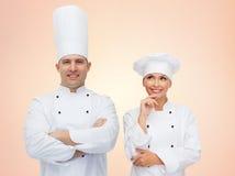 在米黄背景的愉快的厨师或厨师夫妇 免版税库存图片