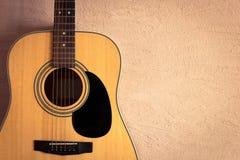 在米黄背景葡萄酒墙壁上的声学吉他 库存照片