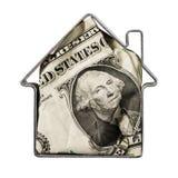 在类似房子的金属形状里面的美元隔绝在白色背景 库存照片