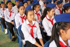 在类期间的高中学生 红色围巾和蓝色贝雷帽是 库存照片