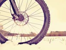 在粉末雪的登山车 在随风飘飞的雪的失去的道路 轮子细节 库存照片