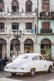 在粉碎的大厦旁边的老汽车在哈瓦那 免版税库存照片