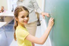 在粉笔板的一点微笑的女小学生文字 免版税库存照片