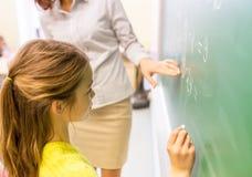 在粉笔板的女小学生和老师文字 库存照片