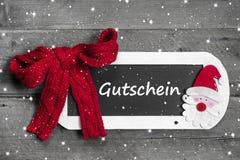在粉笔板的红色弓有优惠券的- Gutschein用德语 免版税库存图片