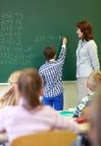 在粉笔板的老师和男小学生文字 库存照片