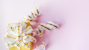 在粉红彩笔背景的白色镶边丝带包裹的礼物盒 r 库存图片