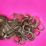在粉红色的卷曲棕色头发 免版税图库摄影