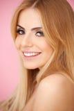 在粉红色的微笑的白肤金发的少妇 图库摄影