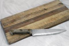 在粒状古板的切板的木刀子 免版税库存图片
