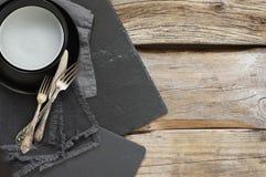 在粗砺的困厄的木桌上的灰色厨房器物 免版税库存图片