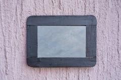在粗砺的墙壁上的板岩板 库存图片