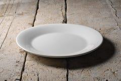 在粗砺的木桌上的空的白色圆的板材 库存照片