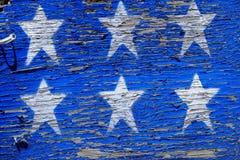在粗砺的木头的被绘的蓝星 库存照片