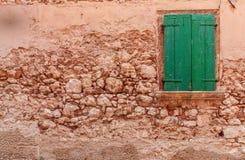 在粗糙的石墙上的看法有闭合的绿色木窗口shutte的 库存图片