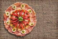 在粗糙的难看的东西粗麻布背景设置的开胃菜美味盘 免版税图库摄影