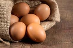 在粗麻布大袋的新近地下的有机鸡蛋在木头 库存照片