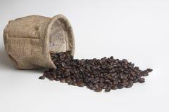 在粗麻布袋的咖啡豆在白色背景 库存图片