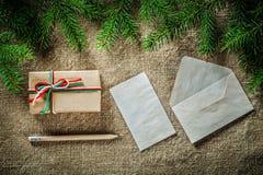 在粗麻布backgro的杉树分支手工制造礼物盒纸铅笔 免版税库存图片
