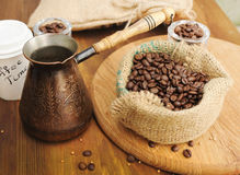 在粗麻布大袋和土耳其咖啡罐的咖啡豆 免版税库存图片