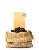 在粗麻布大袋和价牌的烤咖啡豆 图库摄影