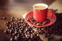 在粗麻布大袋的咖啡杯用烤豆 图库摄影