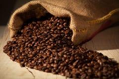在粗麻布大袋的咖啡豆反对黑暗的木头 免版税库存照片