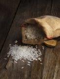 在粗麻布大袋的白色长的米在木桌上 库存照片
