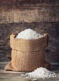 在粗麻布大袋的米在木背景 免版税库存照片