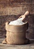 在粗麻布大袋的米有在木背景的瓢的 图库摄影