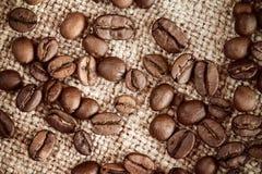 在粗麻布大袋背景的咖啡豆 库存照片