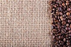 在粗麻布大袋背景的咖啡 免版税库存照片