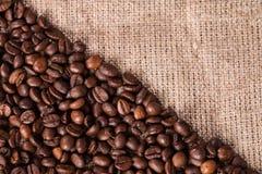 在粗麻布大袋背景的咖啡 库存照片