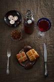 在粗麻布桌布供应的复活节晚餐 肉、十字面包、朱古力蛋和酒 免版税图库摄影