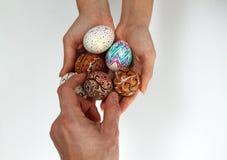 在粗麻布的五颜六色的复活节彩蛋,女性手选择了并且采摘一个鸡蛋 免版税库存照片