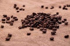 在粗麻布的布朗咖啡粒 库存照片