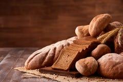在粗麻布的新近地被烘烤的面包大面包在与褐色的木桌上弄脏了背景 纹理特写镜头面包店产品 图库摄影