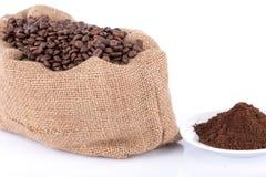 在粗麻布袋和咖啡粉末的咖啡豆 免版税库存照片