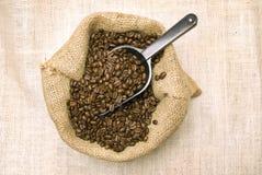 在粗麻布袋的咖啡豆与瓢 免版税库存照片