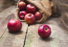 在粗麻布袋的红色苹果在木背景 免版税库存照片
