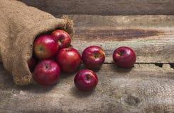 在粗麻布袋的红色苹果在木背景 免版税图库摄影