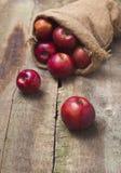 在粗麻布袋的红色苹果在木背景 图库摄影