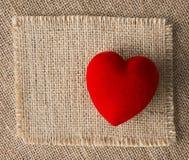 在粗麻布,麻袋布背景的红色心脏 红色上升了 库存图片