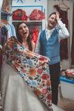 在精品店的年轻婚姻的夫妇买的衣裳 免版税库存图片