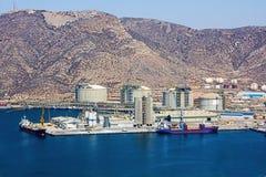 在精炼厂旁边的大船只负荷 图库摄影