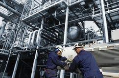 在精炼厂里面的油和煤气工作者 免版税库存图片