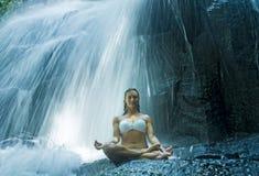 在精神放松平静和凝思的妇女坐的莲花瑜伽姿势在B的惊人的美丽的瀑布和雨林 库存图片