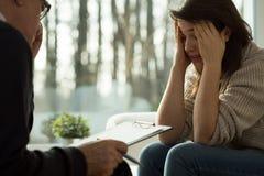 在精神疗法会议期间的愁苦的女孩 图库摄影
