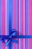 在糖果条纹包装纸背景的蓝色礼物丝带弓,垂直 库存图片