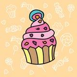 在糖果背景的逗人喜爱的杯形蛋糕 图库摄影